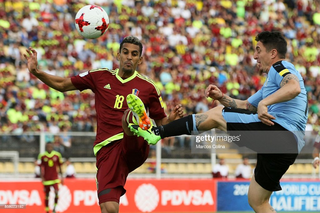 Victor Garcia of Venezuela fights for the ball with Cristian Rodriguez of Uruguay during a match between Venezuela and Uruguay as part of FIFA 2018 World Cup Qualifiers at Pueblo Nuevo Stadium on October 05, 2017 in San Cristobal, Venezuela.