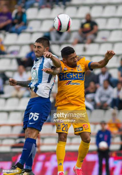 Victor Guzman of Pachuca jumps for the ball with Javier Aquino of Tigres during their Mexican Apertura 2017 Tournament football match at Hidalgo...