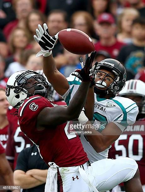 Victor Hampton of the South Carolina Gamecocks breaks up a pass to Seun Olukoju of the Coastal Carolina Chanticleers during their game at...