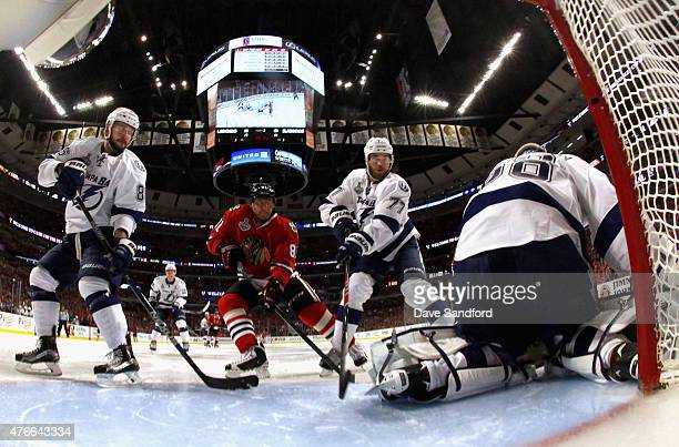 Victor Hedman and Nikita Kucherov of the Tampa Bay Lightning and Marian Hossa of the Chicago Blackhawks watch as goaltender Andrei Vasilevskiy makes...