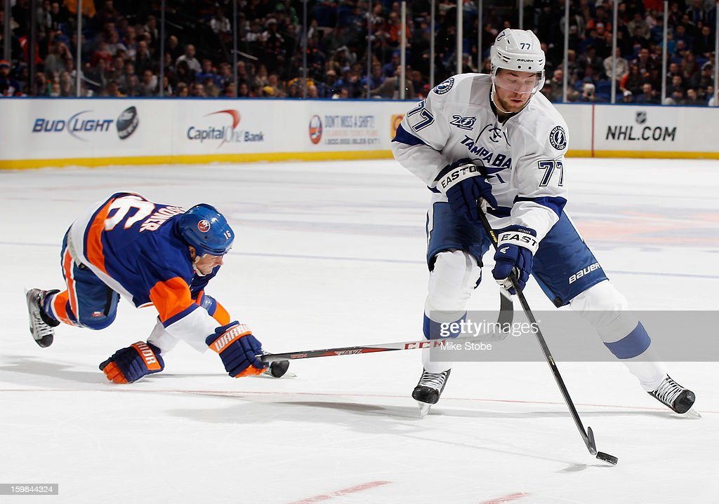 Victor Hedman #77 of the Tampa Bay Lightning plays the puck as Marty Reasoner #16 of the New York Islanders of the New York Islanders looses his footing at Nassau Veterans Memorial Coliseum on January 21, 2013 in Uniondale, New York.