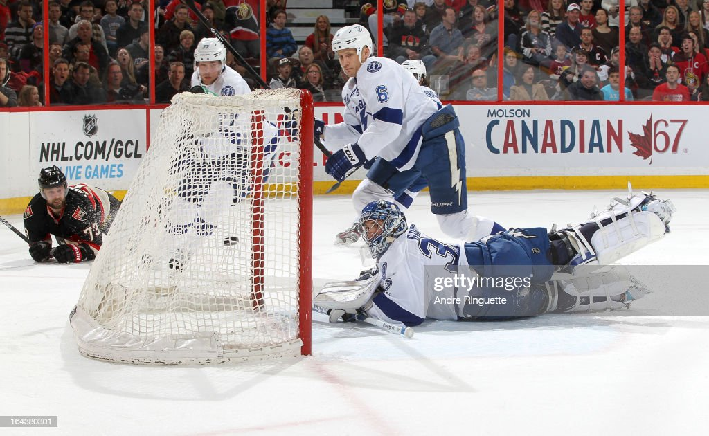 <a gi-track='captionPersonalityLinkClicked' href=/galleries/search?phrase=Victor+Hedman&family=editorial&specificpeople=4784238 ng-click='$event.stopPropagation()'>Victor Hedman</a> #77, <a gi-track='captionPersonalityLinkClicked' href=/galleries/search?phrase=Sami+Salo&family=editorial&specificpeople=206132 ng-click='$event.stopPropagation()'>Sami Salo</a> #6 and <a gi-track='captionPersonalityLinkClicked' href=/galleries/search?phrase=Mathieu+Garon&family=editorial&specificpeople=206119 ng-click='$event.stopPropagation()'>Mathieu Garon</a> #32 of the Tampa Bay Lightning watch the puck go into the net for a first period goal by <a gi-track='captionPersonalityLinkClicked' href=/galleries/search?phrase=Guillaume+Latendresse&family=editorial&specificpeople=848999 ng-click='$event.stopPropagation()'>Guillaume Latendresse</a> #73 of the Ottawa Senators on March 23, 2013 at Scotiabank Place in Ottawa, Ontario, Canada.