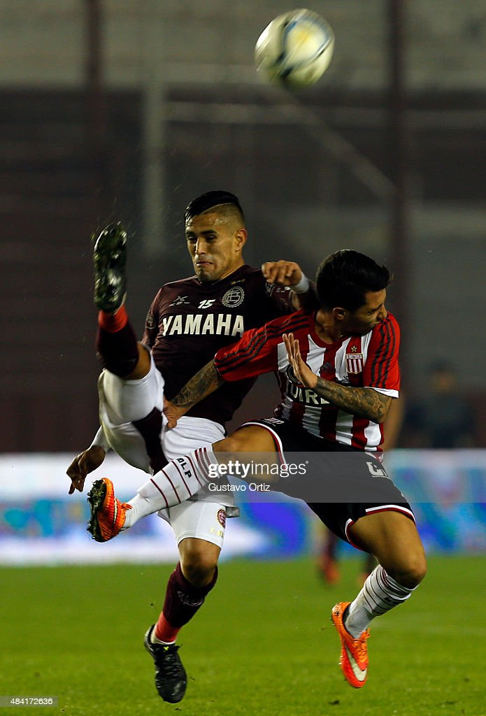 Victor Hugo Ayala of Lanus and Luciano Acosta of Estudiantes jump for the ball during a match between Lanus and Estudiantes as part of 20th round of Torneo Primera Division 2015 at Ciudad de Lanus Stadium on August 15, 2015 in Lanus, Argentina.