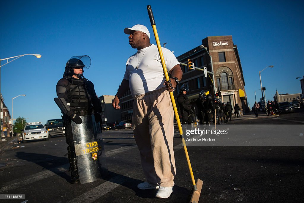 Victor Huntleyel greets Maryland state troopers standing guard near a CVS pharmacy that was set on fire yesterday during rioting after the funeral of...