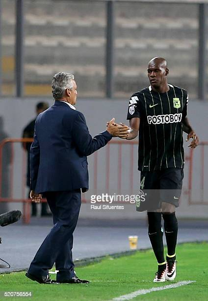 Victor Ibarbo of Atletico Nacional celebrates with his coach Reynaldo Rueda the first goal of his team against Sporting Cristal during a match...