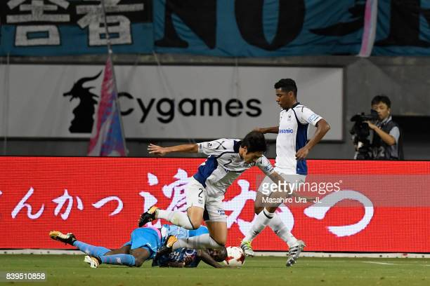Victor Ibarbo of Sagan Tosu is challenged by Genta Miura of Gamba Osaka in the penalty area resulting in a penalty kick during the JLeague J1 match...