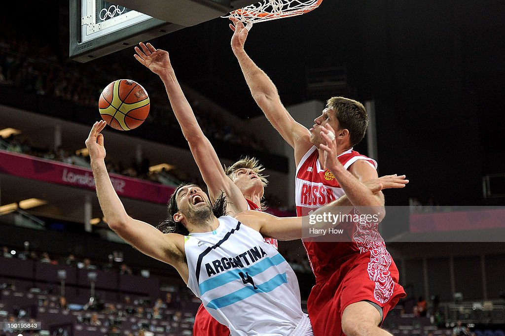 Victor Khryapa of Russia attempts to block Luis Scola of Argentina of Russia during the Men's Basketball bronze medal game between Russia and...