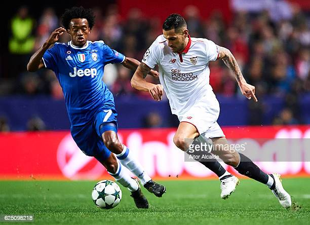 Victor Machin Perez 'Vitolo' of Sevilla FC competes for the ball with Juan Cuadrado of Juventus during the UEFA Champions League match between...