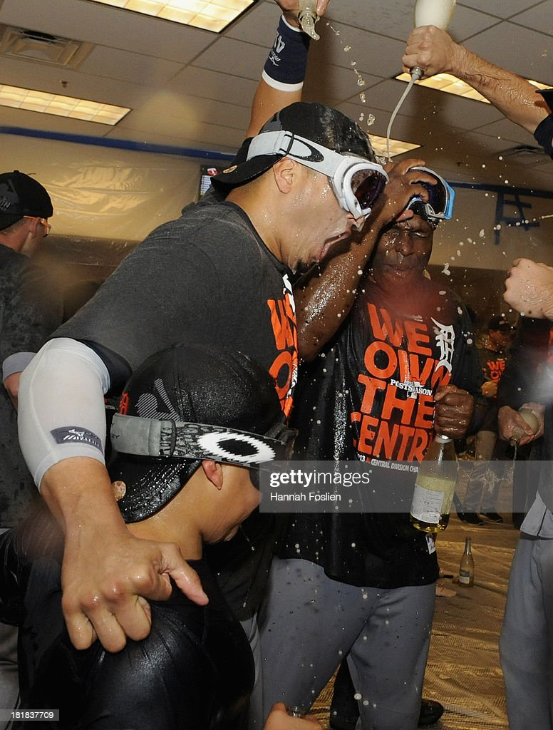 Victor Martinez #41 and Torii Hunter #48 of the Detroit Tigers celebrate with champagne in the clubhouse with Martinez's son Victor Jose after the Tigers defeated the Twins 1-0 on September 25, 2013 at Target Field in Minneapolis, Minnesota. The Tigers clinched the American League Central Division title.