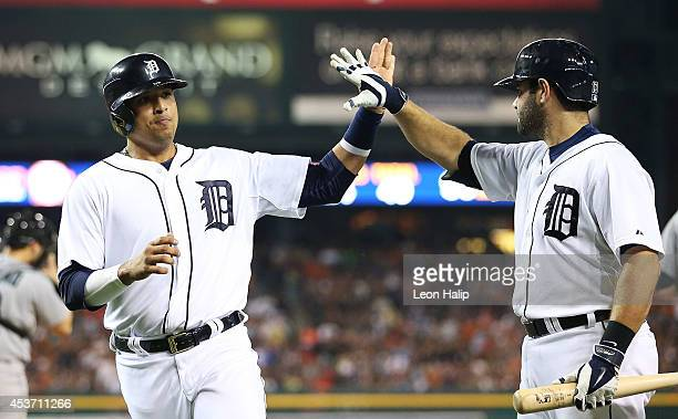 Victor Martinez of the Detroit Tgers celebrates with teammate Alex Avila after scoring on the Nick Castellanos single to center field during the...