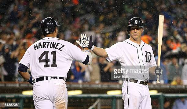 Victor Martinez of the Detroit Tigers celebrates with teammate Andy Dirks after hitting a tworun home run scoring Prince Fielder in the fifth inning...