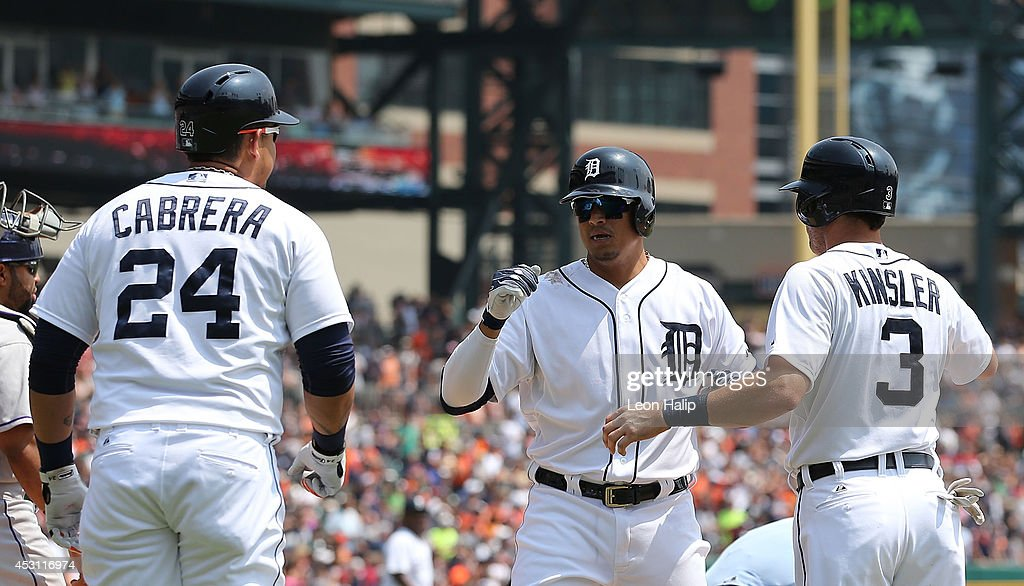 Victor Martinez #41 of the Detroit Tigers celebrates with teammates Miguel Cabrera #24 and Ian Kinsler #3 after hitting a three run home run to left field during the third inning of the game against the Colorado Rockies at Comerica Park on August 3, 2014 in Detroit, Michigan.