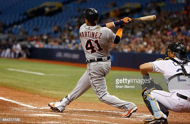Victor Martinez of the Detroit Tigers hits a threerun home run in front of catcher Hank Conger of the Tampa Bay Rays during the seventh inning of a...