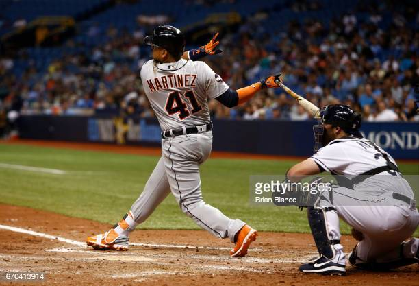 Victor Martinez of the Detroit Tigers hits a tworun single in front of catcher Derek Norris of the Tampa Bay Rays during the fifth inning of a game...