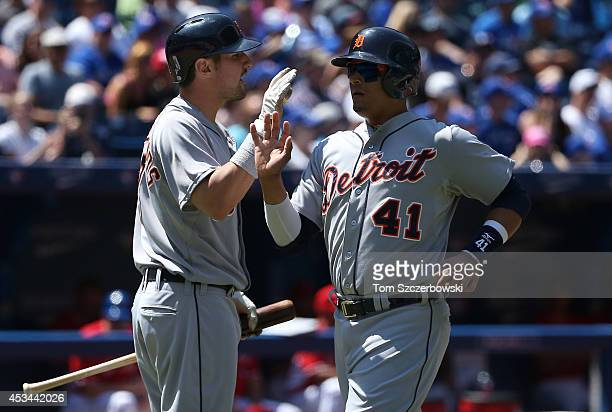 Victor Martinez of the Detroit Tigers is congratulated by Nick Castellanos after scoring a run in the first inning during MLB game action against the...
