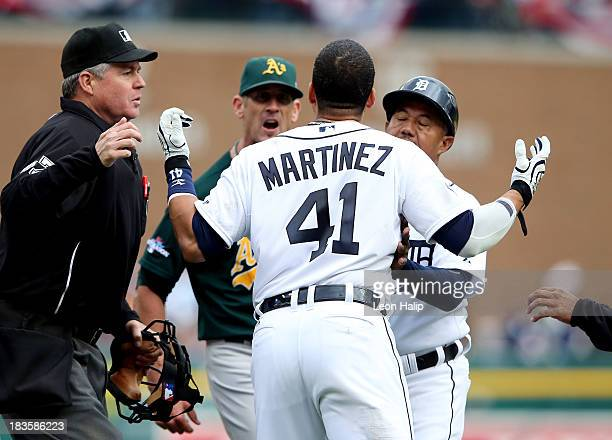 Victor Martinez of the Detroit Tigers is held back while exchanging words with Grant Balfour of the Oakland Athletics in the ninth inning of Game...