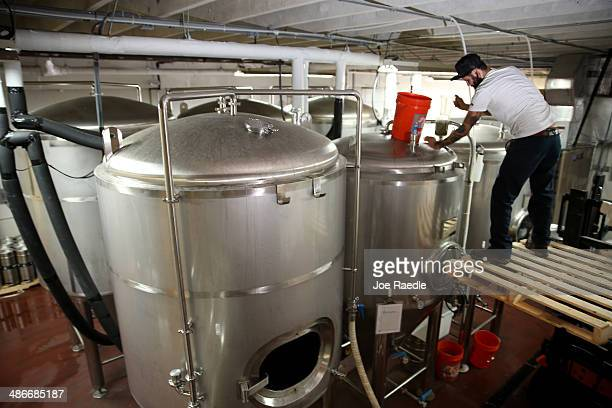 Victor Mesa a beer brewer puts hops into a beer fermenting tank at Wynwood Brewing Company on April 25 2014 in Miami Florida Earlier this week...
