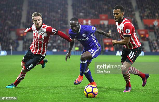 Victor Moses of Chelsea is challenged by Steven Davis of Southampton and Ryan Bertrand of Southampton during the Premier League match between...