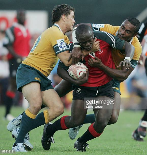 Victor Oduor of Kenya is tackled by Arthur Little and Viliame Ratu of Australia during the Emirates IRB 7's at the Dubai Exiles Rugby Ground on...
