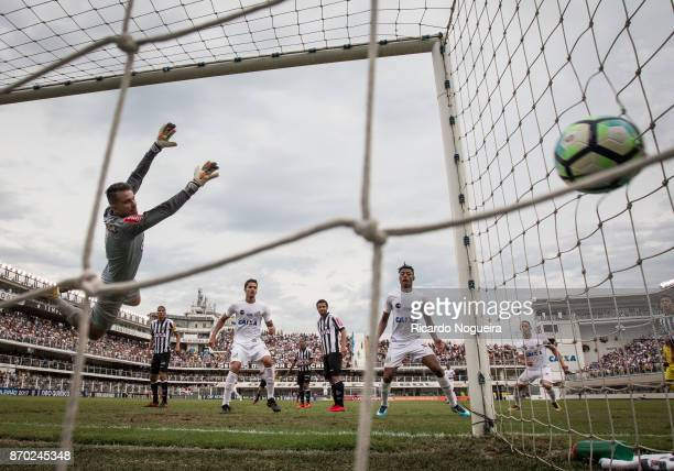 Victor of Atletico Mineiro jumps but can not reach the ball headed by David Braz of Santos during the match between Santos and Atletico Mineiro as a...