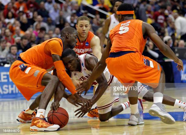 Victor Oladipo of the Indiana Hoosiers fights for the loose ball against Baye Keita Brandon Triche and CJ Fair of the Syracuse Orange during the East...