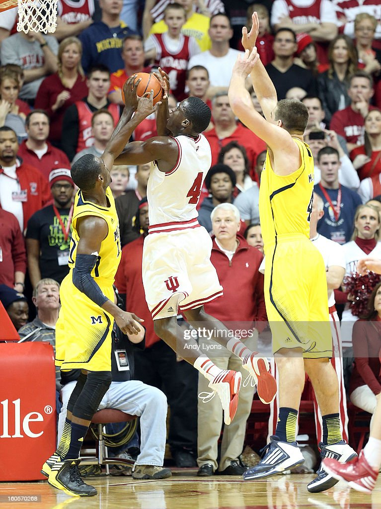 Victor Oladipo #4 of the Indiana Hoosiers shoots the ball while defended by Tim Hardaway Jr #10 and Mitch McGary #4 of the Michigan Wolverines during the game at Assembly Hall on February 2, 2013 in Bloomington, Indiana.