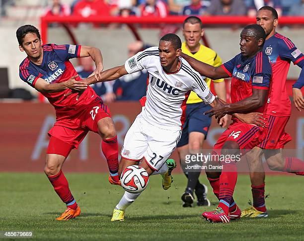 Victor Pineda and Jhon Kennedy Hurtado of the Chicago Fire try to hold back Jerry Bengtson of the New England Revolution during an MLS match at...