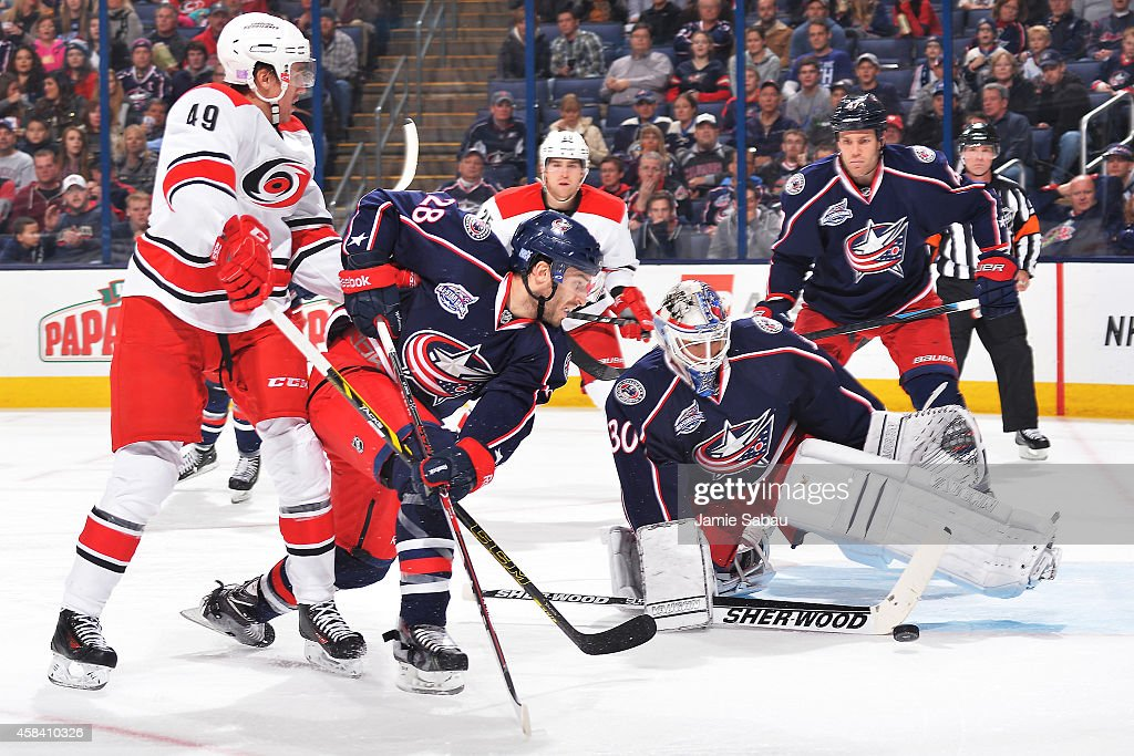 Victor Rask of the Carolina Hurricanes and Frederic StDenis of the Columbus Blue Jackets battle for control of the puck as goaltender Curtis...