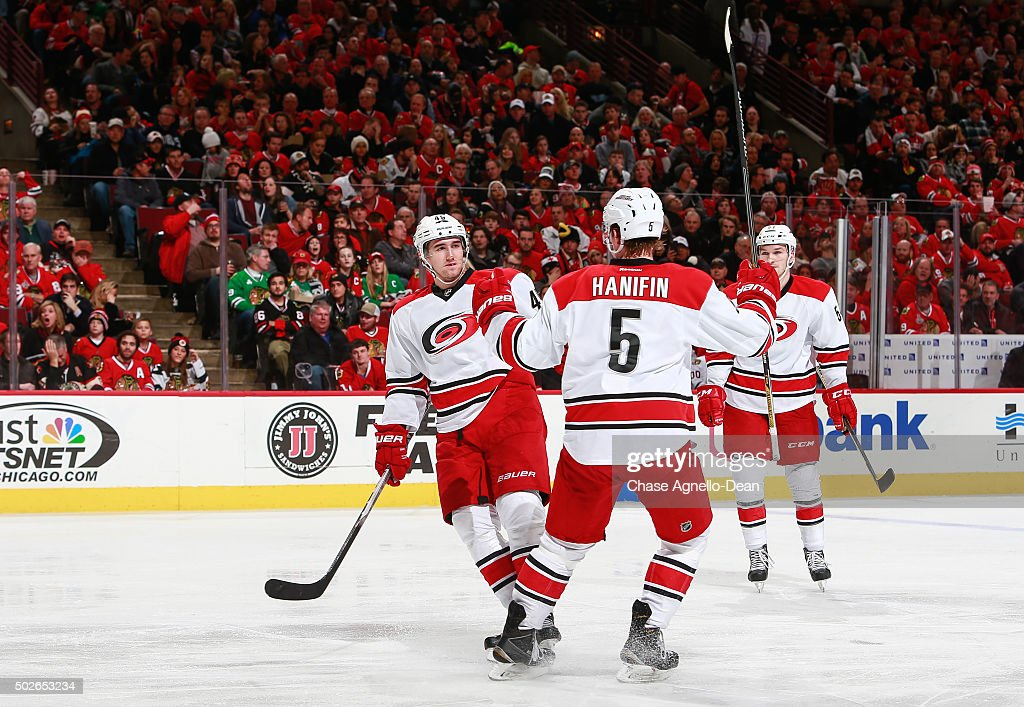 Victor Rask #49 of the Carolina Hurricanes celebrates with Noah Hanifin #5 after scoring in the third period of the NHL game against the Chicago Blackhawks at the United Center on December 27, 2015 in Chicago, Illinois.