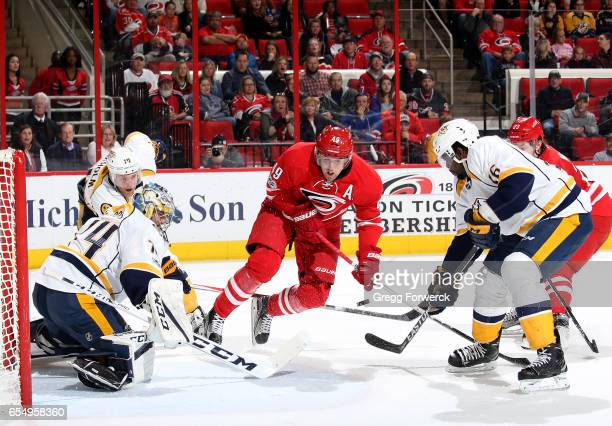 Victor Rask of the Carolina Hurricanes crashes the crease and puts a shot on goal as Juuse Saros of the Nashville Predators makes the save and...
