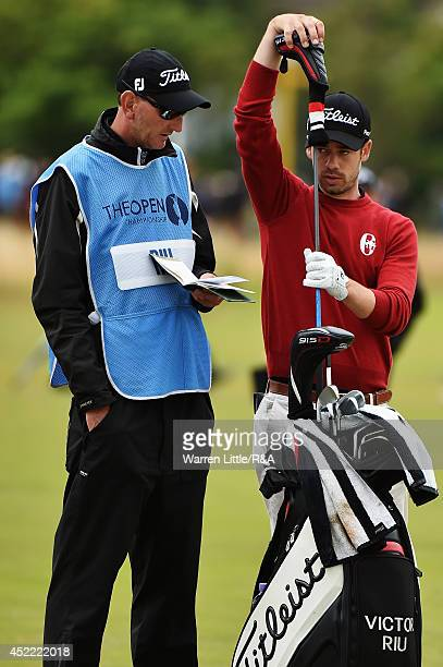 Victor Riu of France pulls a club from his bag alongside his caddie during a practice round prior to the start of the 143rd Open Championship at...