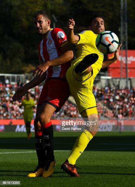 Victor Ruiz of Villarreal CF competes for the ball with Cristhian Stuani of Girona FC during the La Liga match between Girona and Villarreal at...