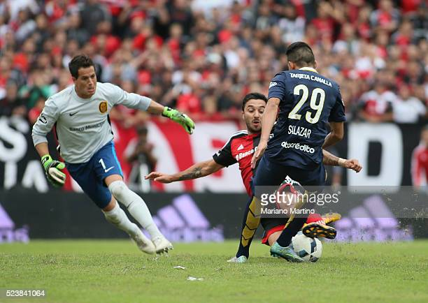 Victor Salazar of Central slides to prevent the goal by Ignacio Scocco of Newell's after he had left Sebastian Sosa of Central behind during a match...