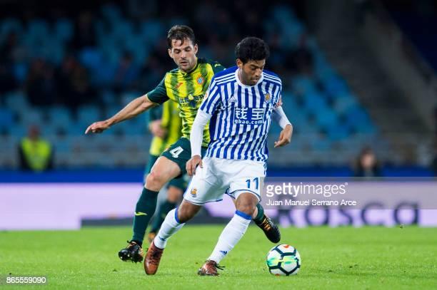 Victor Sanchez of RCD Espanyol duels for the ball with Carlos Vela of Real Sociedad during the La Liga match between Real Sociedad de Futbol and RCD...
