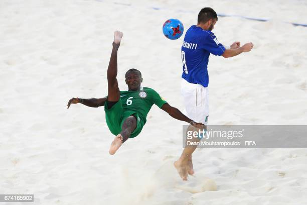 Victor Tale of Nigeria attempts a scissor or bicycle kick shot on goal as Francesco Corosiniti of Italy defends during the FIFA Beach Soccer World...