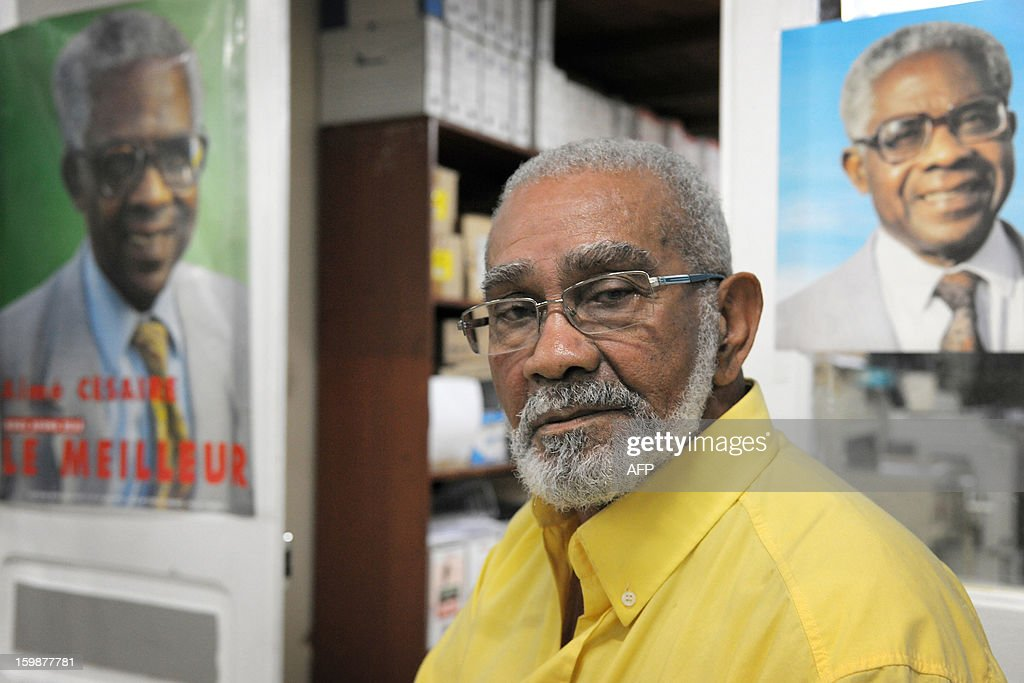 Victor Tisserand, 85, a supporter of the Martinican Progressive Party (PPM), poses in front of two portraits of late French poet and politician Aime Cesaire, which he met for more than fifty years, on January 21, 2013 at the PPM headquarters in Fort-de-France, on the French Caribbean island of Martinique, during the launch of celebrations marking the 100th anniversary of Cesaire's birth. French poet Aime Cesaire (June 25, 1913 – 17 April 2008) was former mayor of Fort-de-France and funded the PPM party in 1958. As a pioneer of the black pride movement, Cesaire was a cult figure on his native island of Martinique and in the French-speaking world. With fellow writers such as Leopold Sedar Senghor of Senegal, 'Papa Cesaire' invented the term 'negritude,' which he defined as an 'affirmation that one is black and proud of it', decades before the emergence of Steve Biko or Martin Luther King. AFP PHOTO / JEAN-MICHEL ANDRE