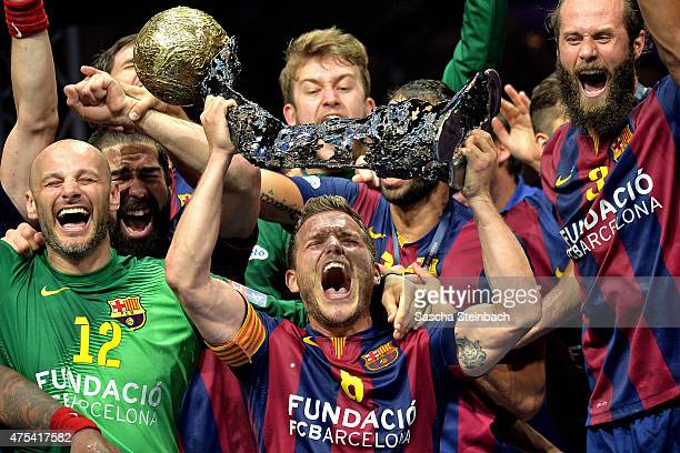 Victor Tomas Gonzalez of Barcelona receives the trophy after winning the 'VELUX EHF FINAL4' final match against MKBMVM Veszprem at Lanxess Arena on...