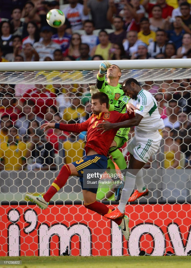 Victor Valdes and Gerard Pique of Spain battle for the ball with Godfrey Oboabona of Nigeria during the FIFA Confederations Cup Brazil 2013 Group B match between Nigeria and Spain at Castelao on June 23, 2013 in Fortaleza, Brazil.