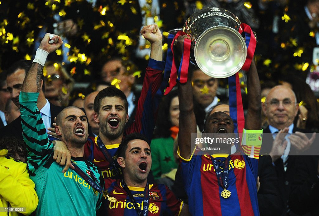 Victor Valdes, <a gi-track='captionPersonalityLinkClicked' href=/galleries/search?phrase=Gerard+Pique&family=editorial&specificpeople=227191 ng-click='$event.stopPropagation()'>Gerard Pique</a> and Xavi celebrate as teammate Eric Abidal of FC Barcelona lifts the trophy during the UEFA Champions League final between FC Barcelona and Manchester United FC at Wembley Stadium on May 28, 2011 in London, England.