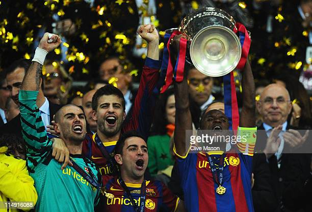 Victor Valdes Gerard Pique and Xavi celebrate as teammate Eric Abidal of FC Barcelona lifts the trophy during the UEFA Champions League final between...