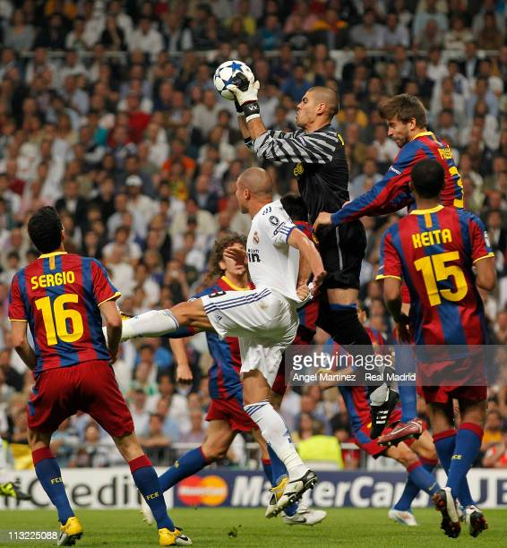 Victor Valdes of Barcelona catches the ball beside Pepe of Real Madrid during the UEFA Champions League Semi Final first leg match between Real...
