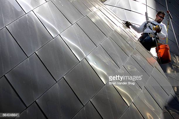 Victor Velasquez hangs from a rope tethered to the top of the Walt Disney Concert Hall while working to sand down the shiny stainless surface of the...