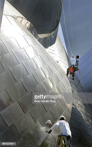 Victor Velasquez hangs from a rope top while coworker James Groff stands atop a ladder as both men work to sand down the shiny stainless surface of...