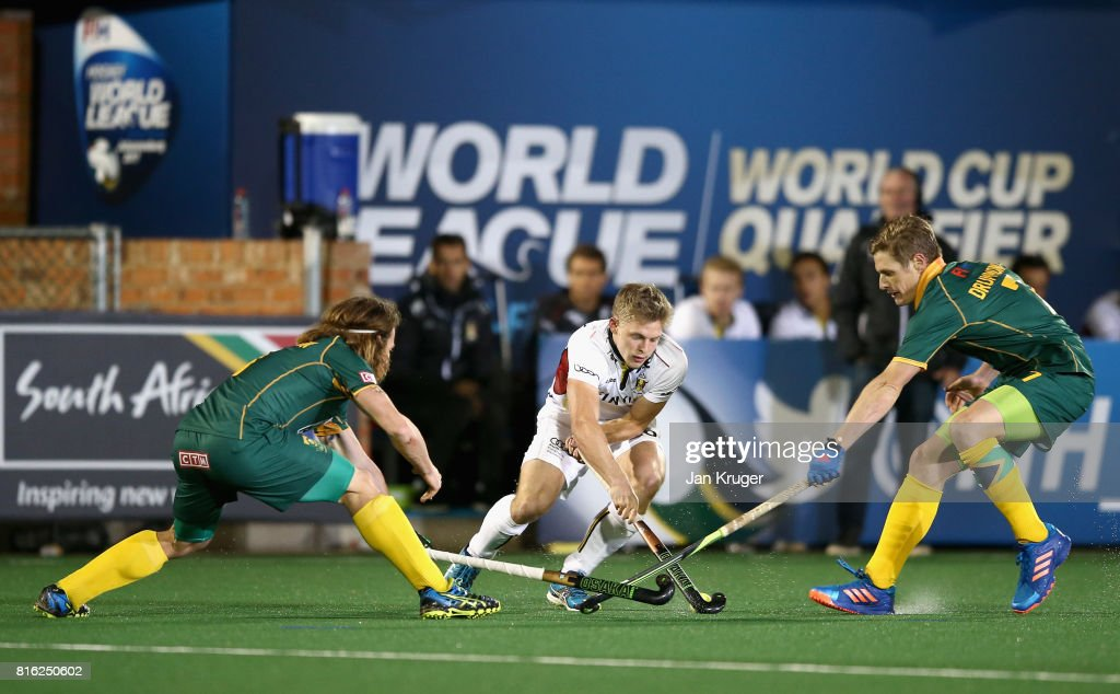 Victor Wegnez of Belgium attempts to keep the ball while under pressure from Jonathan Robinson of South Africa (L) and Tim Drummond of South Africa (R) during the Group B match between South Africa and Belgium on day five of the FIH Hockey World League - Men's Semi Finals on July 17, 2017 in Johannesburg, South Africa.