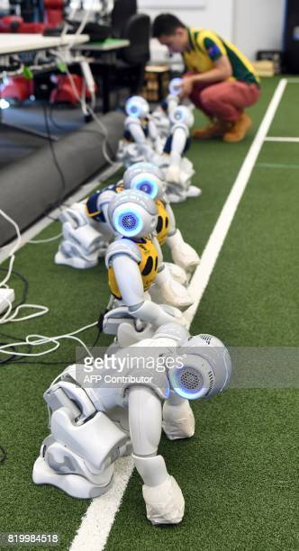 Victor Wong unplugs a soccer robot in Sydney on July 21 as Australias fivetime world champions of robot soccer the University of New South Wales'...