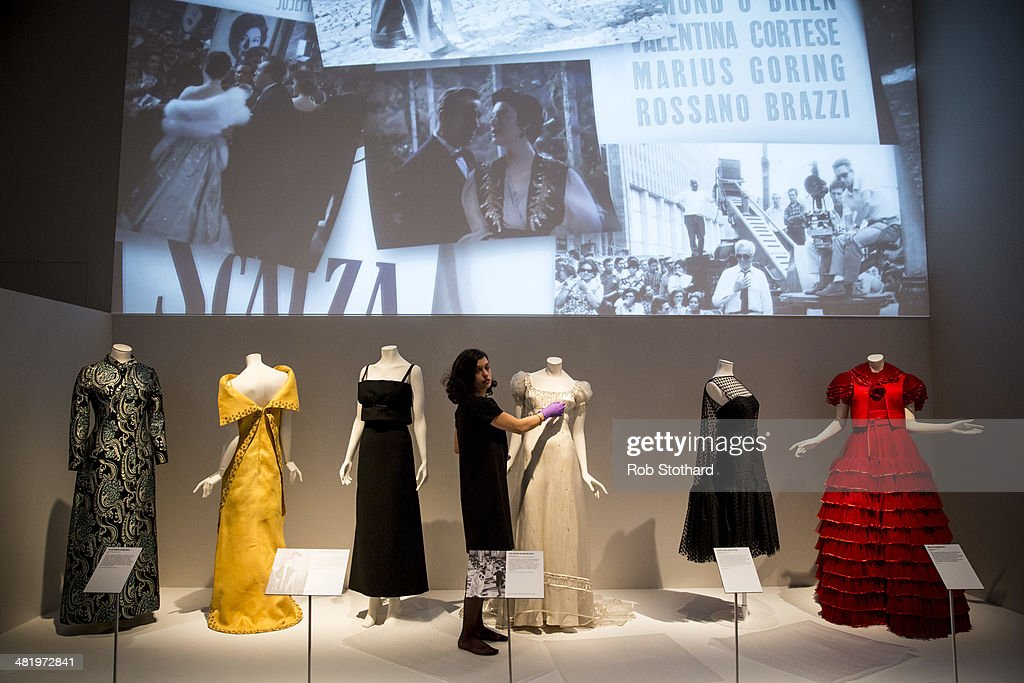 Victoria and Albert Museum employee adjusts dresses on display ahead of The Glamour of Italian Fashion 19452014 exhibition on April 2 2014 in London...