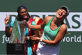 Victoria Azarenka of Belarus laughs with the winners trophy as Serena Williams of USA pulls a face after the final during day fourteen of the BNP...