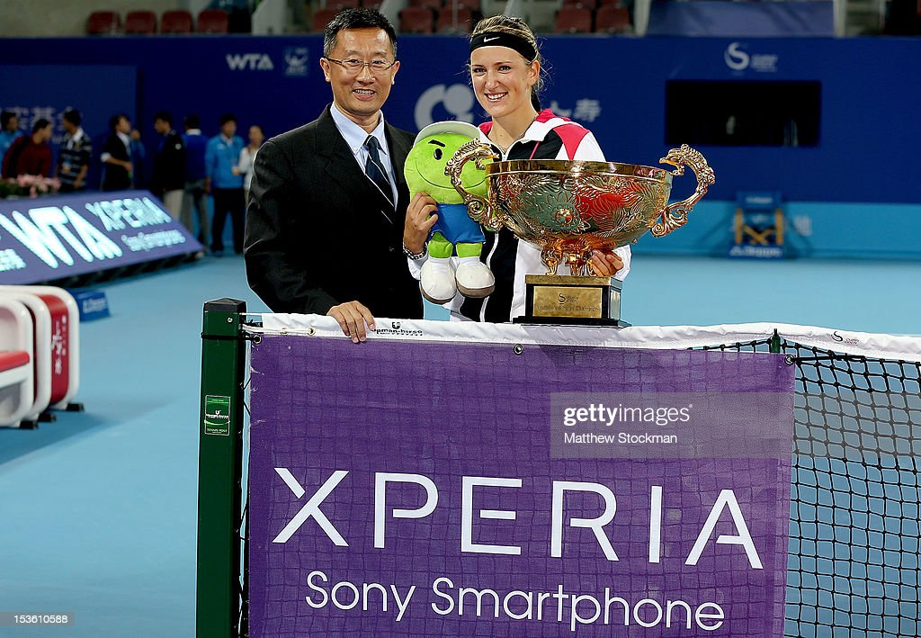 Victoria Azarenka of Belarus poses for photographers with Sony Mobile Communications Vice President Tian Guojin after defeating Maria Sharapova of Russia during the final of the China Open at the China National Tennis Center on October 7, 2012 in Beijing, China.