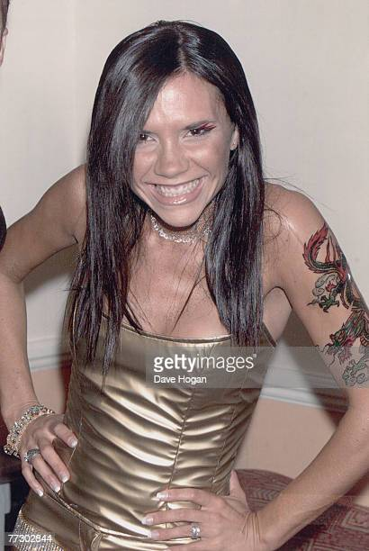 Victoria Beckham of British pop group the Spice Girls sports a nonpermanent tattoo of a Chinese dragon on her arm circa 1998