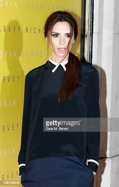 Victoria Beckham poses for cameras to toast her collection launch at Harvey Nichols on February 17 2012 in London United Kingdom